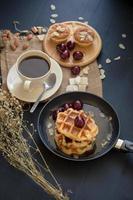 gaufres et cerises au miel, tartes aux amandes croustillantes et une tasse de café sur table noire photo