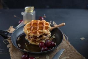 Miel sur des gaufres dans une casserole avec des cerises sur une table en bois sombre