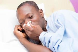 jeune homme avec fièvre malade au lit photo