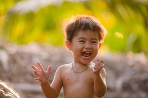 garçon asiatique souriant et jouant avec de leau photo