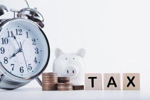 temps de payer les impôts. horloge de tirelire, pièces empilées et bloc de bois sur fond blanc. fiscalité et concept de taxe annuelle photo
