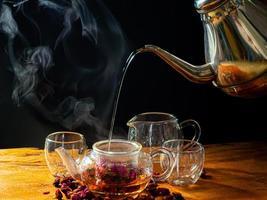 Feuilles de thé rose dans une tasse en verre et théière photo