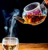 Feuilles de thé rose dans une bouilloire en verre photo