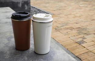 deux mugs de voyage sur béton