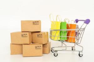 boîtes en papier et sacs à provisions dans un chariot sur fond blanc. achats en ligne ou concept de commerce électronique et concept de service de livraison