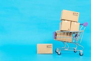 boîtes de papier dans un chariot sur fond bleu. concept de magasinage en ligne ou de commerce électronique et concept de service de livraison avec espace de copie pour votre conception