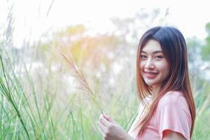 femme asiatique, debout, et, sourire, sur, nature, fond photo