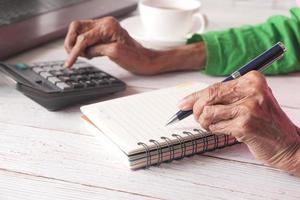 Gros plan de la main de femmes âgées écrit sur le bloc-notes photo