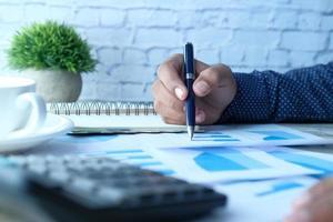 main de l'homme écrit sur un bureau