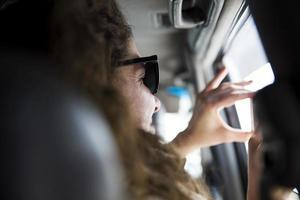 Jeune femme prenant une photo avec un téléphone portable de l'intérieur d'un véhicule lors d'un road trip