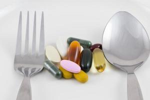 plusieurs comprimés de médicaments sur une assiette avec une cuillère et une fourchette