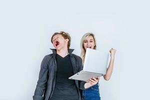 Portrait d'heureux jeune couple à l'aide d'un ordinateur portable en studio