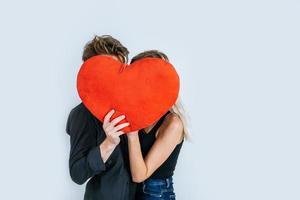 couple heureux aimant ensemble tenant un coeur rouge