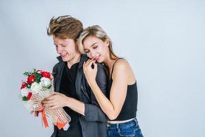 Portrait d'heureux jeune couple avec des fleurs en studio
