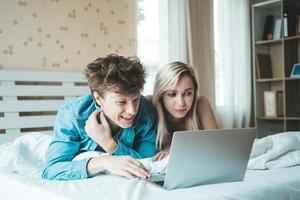 couple heureux utilisant un ordinateur portable sur le lit