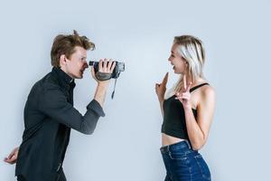 Heureux portrait de couple tenant une caméra vidéo et l'enregistrement d'une vidéo