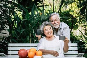 couple de personnes âgées portant et mangeant des fruits