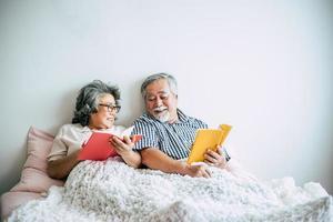 couple de personnes âgées allongé sur le lit et lisant un livre