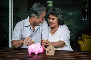 Couple de personnes âgées parlant de finances avec tirelire