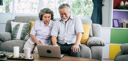 couple de personnes âgées parlant et utilisant un ordinateur portable
