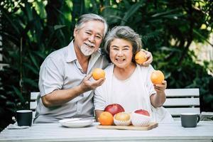 couple de personnes âgées jouant et mangeant des fruits
