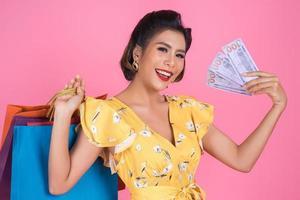 happy f femme à la mode tenant de l'argent pour faire du shopping