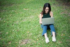 Belle jeune femme assise sur l'herbe verte et utilisant un ordinateur portable dans le parc
