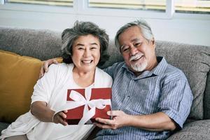 Couple de personnes âgées surprend avec boîte-cadeau dans le salon