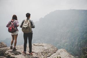 couple de randonneurs avec des sacs à dos debout au sommet d'une montagne et profiter de la vue sur la nature