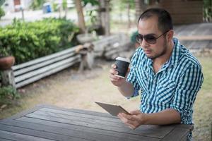 jeune homme est assis à l'extérieur à une table en bois et se détendre avec tablette