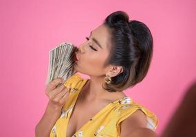 heureuse femme à la mode tenant de l'argent pour faire du shopping