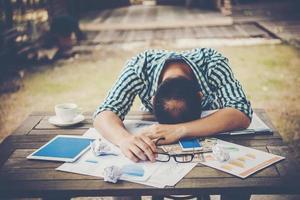 Homme de travail fatigué dormir sur le lieu de travail plein de travail photo