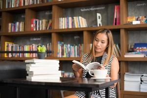 femme asiatique, lecture livre, dans, bibliothèque