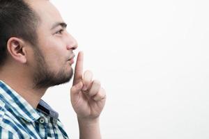 Jeune homme faisant un geste de silence isolé sur fond blanc photo