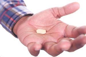 Gros plan de la main de l'homme tenant une pilule isolé sur fond blanc photo