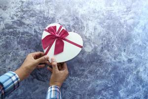 Vue de dessus d'un homme tenant une boîte en forme de coeur photo