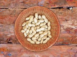 Arachides dans un panier en osier sur fond de bois photo