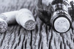 photo en noir et blanc d'une bouteille de vin et de bouchons