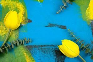 tulipes jaunes fraîches avec des feuilles d'eucalyptus à plat sur abstrait coloré photo