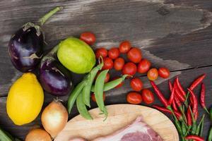 Steak non cuit sur une planche à découper en bois avec des oignons, du persil, de l'aneth, des piments, des haricots verts et un citron sur une table en bois sombre photo