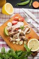 Porc grillé et garnitures sur planche à découper en bois avec oignons, ail, tomates, haricots verts, citron et citron vert sur une nappe colorée sur une table en bois sombre photo