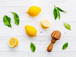 Citrons et un presse-agrumes sur un fond blanc minable photo