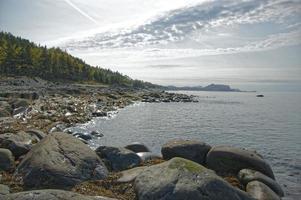 Rochers et rivage à côté de plan d'eau avec ciel bleu nuageux au Québec, Canada photo