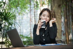 Jeune femme d'affaires appréciant le café pendant le travail sur un ordinateur portable photo