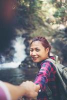 jeune couple aventure femme guidant l'homme dans le concept de voyage de la forêt. photo