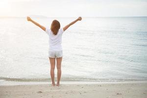 L'arrière de la jeune femme debout étirer ses bras en l'air sur la plage pieds nus photo