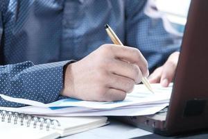 main de l'homme écrit sur le dessus du bureau