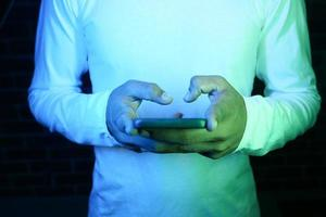 gros plan, de, jeune homme, main, utilisation, a, téléphone intelligent, soir photo