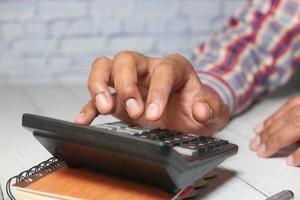 gros plan de la main de l'homme à l'aide de la calculatrice