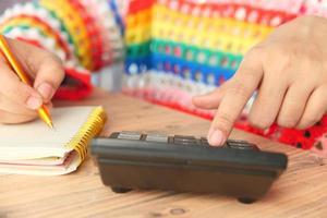 Les jeunes femmes en robe colorée à l'aide de la calculatrice sur le bureau